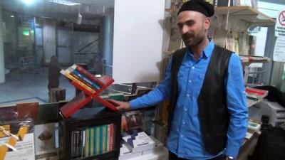 Dükkanına astığı espirili afişlerle insanları kitaplara çekmeye çalışıyor
