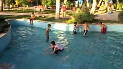 Sıcaktan bunalan çocuklar süs havuzlarında serinliyor