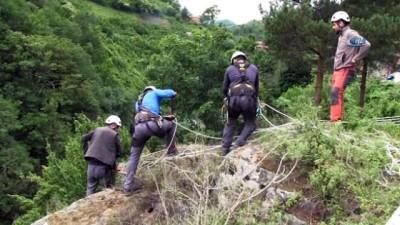 Yerinden kopmak üzere olan kayayı tedbirli bir şekilde yola indirdiler
