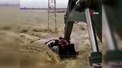 Sel sularına gömülen otomobildeki iki kişinin kepçeyle kurtarılma anı kamerada