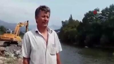 sudan -  Tuttuğu balığı kiraladığı kepçe ile sudan çıkarttı