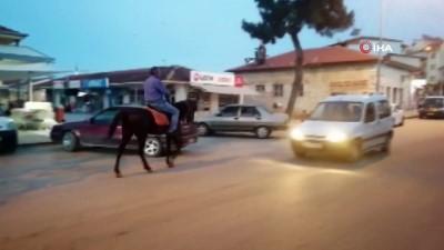 İlçe meydanında atla dolaşıyor... Atıyla sokakları turlayan adam görenleri şaşırtıyor