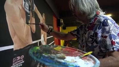 Boş bulduğu duvarlara resim yapıyor